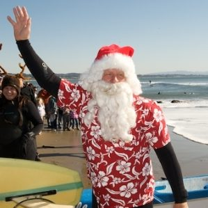 Surfing Santa waves to the crowd_web small - Capitola Soquel Chamber of Commerce Capitola, CA